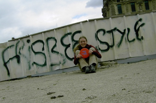 Jenny Cook in front of some Frisbee-themed graffiti in France.